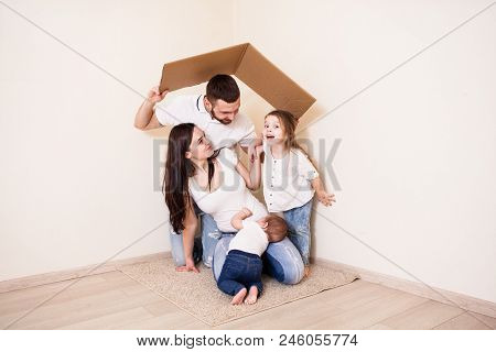 Lovely Family Playing Together, Pretending They Are In The Paper House. Young Family Having Fun Unde