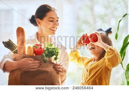 Family shopping. Mother and her daughter are holding grocery shopping bag with vegetables.