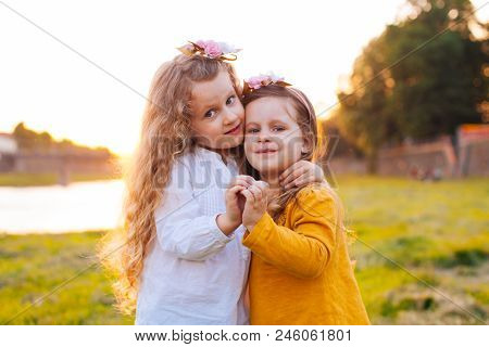 Two Pretty Young Girls Making Heart From Hands In Summer Sunshine