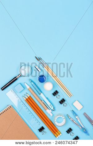 Stationary on blue background. Notebook, pencils, ruler, paints, brushes and other. Knolling concept. poster