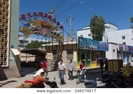 Dunhuang, China - August 7, 2012: Street Scene In The City Of Dunhuang, With People Walking In A Str