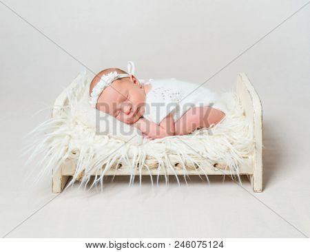 Happy baby girl sleeping on small crib