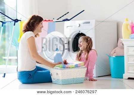 Mother And Kids In Laundry Room With Washing Machine Or Tumble Dryer. Family Chores. Modern Househol