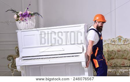 Loader Moves Piano Instrument. Man With Beard, Worker In Overalls And Helmet Lifts Up Piano, White B
