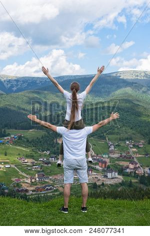 Girl Sits On The Shoulders Of The Guy With Hands Raised. Mountains On The Background. Back View