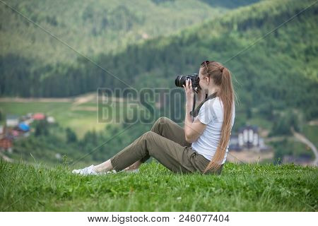 Girl With Camera Sits On A Hill And Mountain Photographs. Summer Day