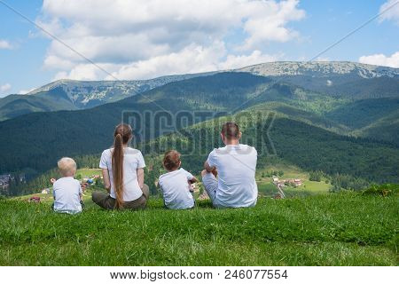 Family Holiday. Parents And Two Sons Admire Views Of The Mountains. Back View. Sunny Summer Day