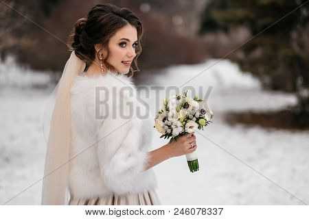 Portrait Of A Beautiful Bride In A Winter Forest. Woman In A Wedding Dress, In A White Fur Coat And
