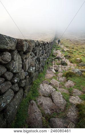 A View Down Slieve Donard Wall Towards A Man Walking Into Low Lying Cloud.