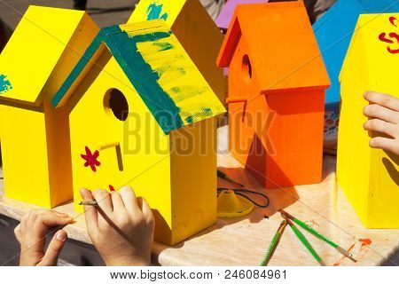 Children Painting Birdhouses Bright Colors Of Orange And Yellow. Kids Woodcraft Lesson, Making Woode