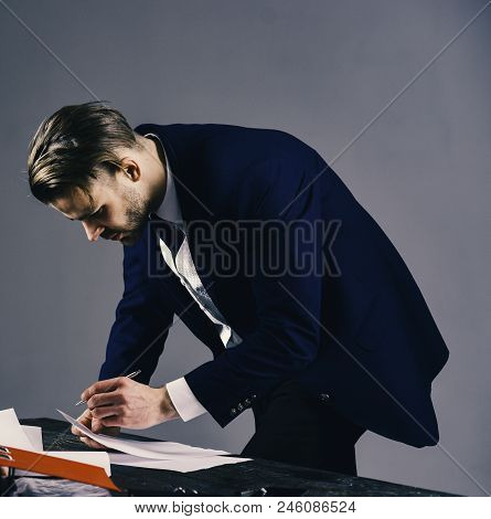 Businessman Signs Contract By Pen On Dark Background. Signing Documents Concept. Man With Serious Fa