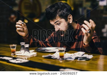 Get high and dope concept. Guy holds rolled banknote, defocused background. Hipster with beard sniffs cocaine, drug. Man with shocked face looking at metal salver with drug. poster