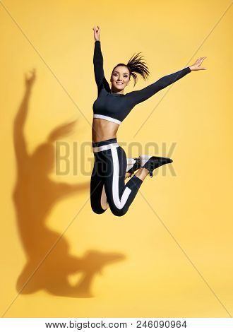 Happy Athletic Woman Jumping Up In Silhouette. Photo Of Sporty Woman In Fashionable Black Sportswear
