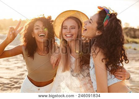 Image of three joyous multiethnic girls 20s in stylish clothing laughing and showing peace sign at camera during beach party at seaside poster