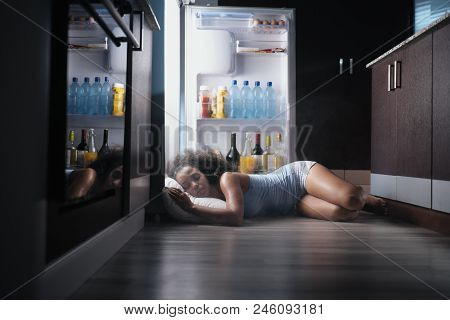 Young Hispanic Woman Suffering For Summer Heat And Lack Of Air Conditioning At Home. Black Girl Cove
