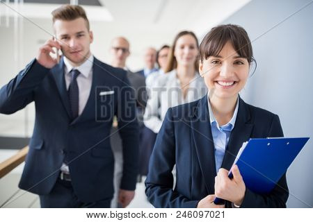 Portrait of female professional holding clipboard while walking with team in office
