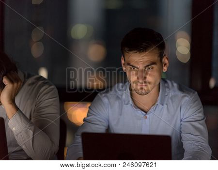 Serious Businessman Working With Team Till Late Night In Low Light From Laptop Screen With Blurred L
