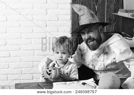 Guy And Boy On White Brick Background. Man In Orange Hat And Kid With Happy And Interested Faces Pla