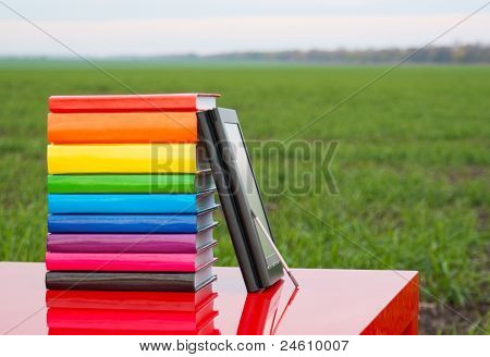 Stack Of Colorful Books And Electronic Book Reader Outdoors