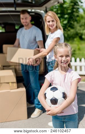 Happy Little Kid Holding Soccer Ball While Her Parents Unpacking Cardboard Boxes For Relocation