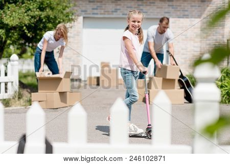 Couple Unpacking Cardboard Boxes While Their Smiling Daughter Riding On Kick Scooter In Front Of New