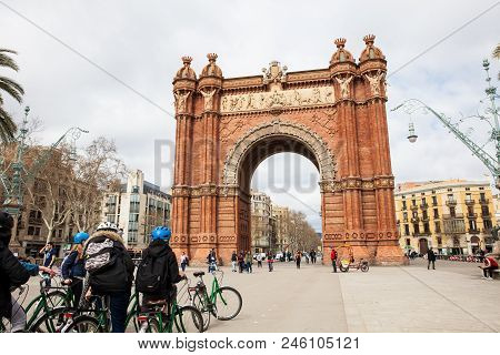 Barcelona - March, 2018: Barcelona - March, 2018: People On A Bike Tour At The Triumphal Arch In Bar
