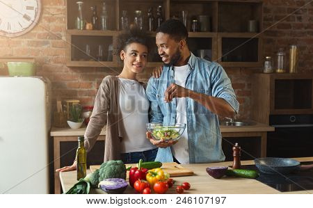 Loving Black Couple Cooking Green Healthy Salad In Loft Interior. Happy Family Cook Vegetarian Food.