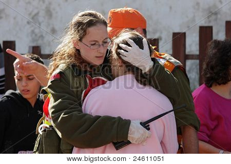 ASHKELON - JANUARY 10: Israeli soldier from rescue team hugs woman who witnessed a missile launched by Hamas terrorists from Gaza explode near her house on January 10, 2009 in Ahskelon, Israel.