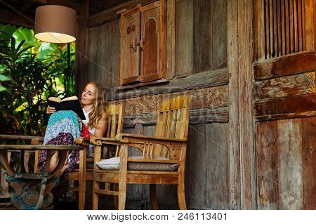 Attractive Girl Sit On Open-air Veranda Of Wooden Bungalow With Tropical Garden View, Read Romance I