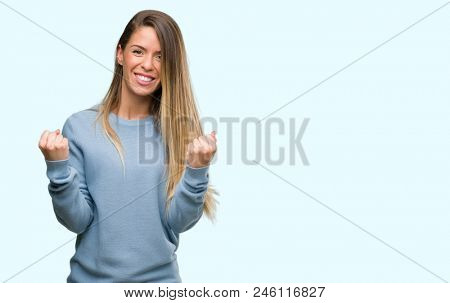 Beautiful young woman wearing sweater and jeans screaming proud and celebrating victory and success very excited, cheering emotion
