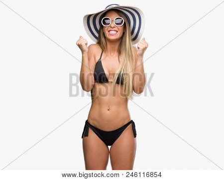 Beautiful young woman wearing bikini, sunglasses and hat excited for success with arms raised celebrating victory smiling. Winner concept.