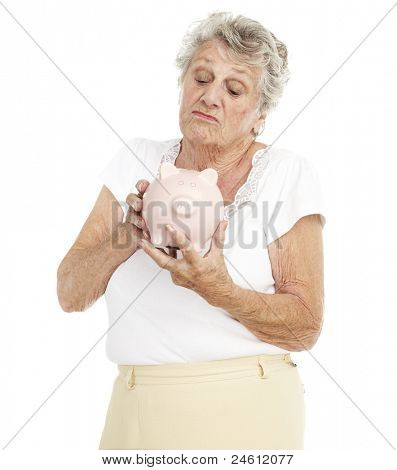 portrait of senior woman looking a piggy bank over white