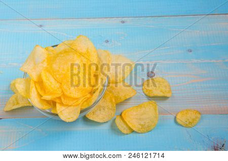 Potato Chips In Bowl On A Blue Wooden Background, Top View. Salty Crisps Scattered On A Table.
