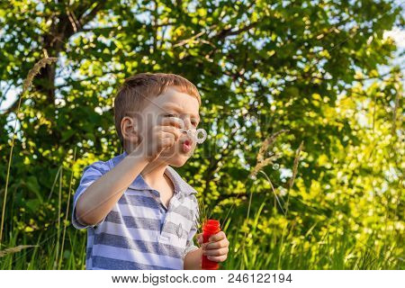 Six-year-old Red-haired Boy Blows Soap In The Park On A Bright, Sunny Summer Day
