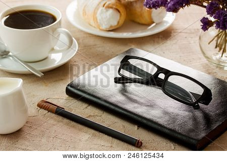 Black Leather Notepad, Black-rimmed Spectacles, Pen With Brown Cap, White Coffee Cup, Rolls With Cre