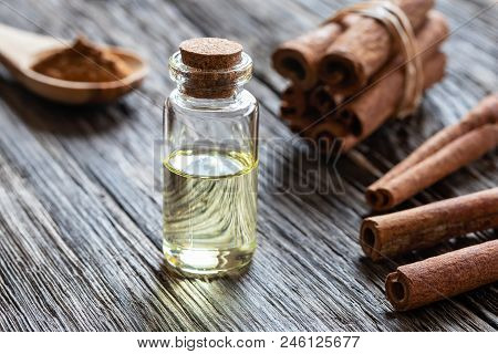A Bottle Of Essential Oil With Cinnamon Bark On A Rustic Background
