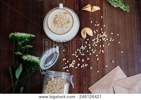 Cappuccino With Pine Nuts On A Wooden Table With Flowers And A Jar Of Nuts.