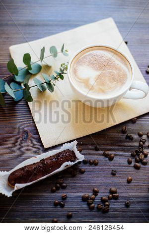 Cup Of Cappuccino On The Wooden Table, Chocolate Eclairs And Eucalyptus.