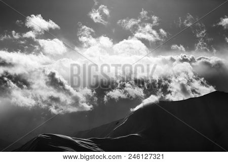 Black and white evening mountain in haze and sunlight clouds. Caucasus Mountains in winter, Georgia, region Gudauri. poster
