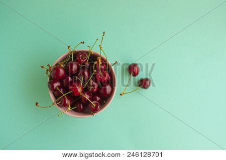 A Bowl With Cherries On Turquoise Background With Space For Your Text.