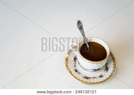 Coffee In The Cup On The Saucer That Stands On The Table, There Is Also A Teaspoon