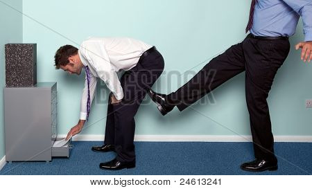 Photo of a businessman bending over to get something out of a drawer as a colleague kicks him up the backside.