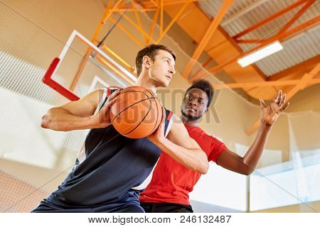 Young Black Man Trying To Stop Contender From Shooting Goal While Playing Basketball Together In Gym