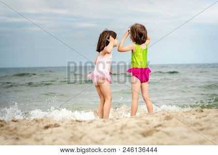 Two Little Girls Sisters Are Standing And Playing On The Sand At The Beach