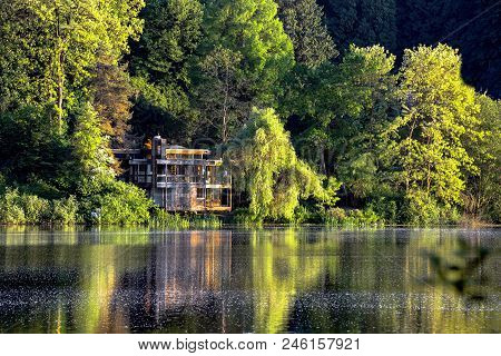 Lonely Little House In The Forest By The Lake. Relaxing Scene,  The House And Trees Are Beautifully