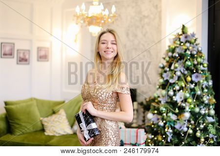 Young Girl With Gift Wearing Dress And Standing Near Christmas Tree. Concept Of Celebrating New Year