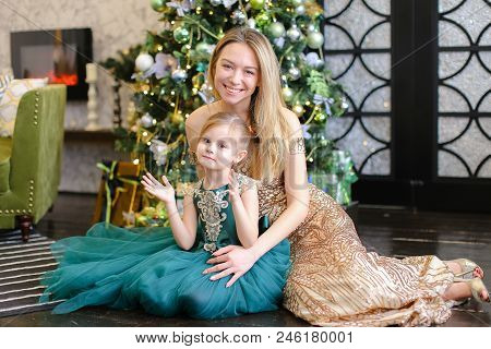 Young American Woman And Little Daughter With Bengal Light Sitting On Floor Near Christmas Tree. Con