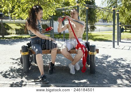 Athletic Caucasian Man And Woman Sitting On The Bench And Wrapping Hands With Bandages For Workout I