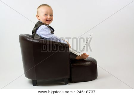 Happy Baby In Leather Chair With Laptop