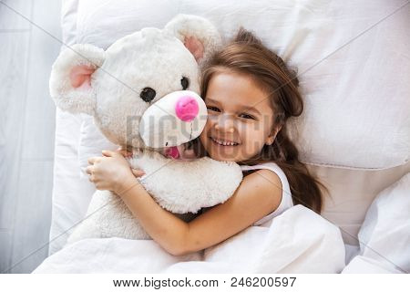 Beautiful Little Girl Hugging Her Teddy Bear In Bed